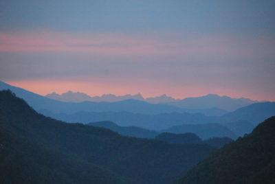 Hrebene Nízkych a Vysokých Himalájí (na obzore) v rannom opare východne od Pokhary.