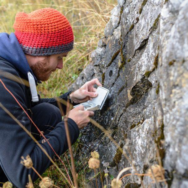 Orientovanie vzoriek v teréne pomocou geologického kompasu. / Orientiation of samples in the field by using a magnetic geological compass.